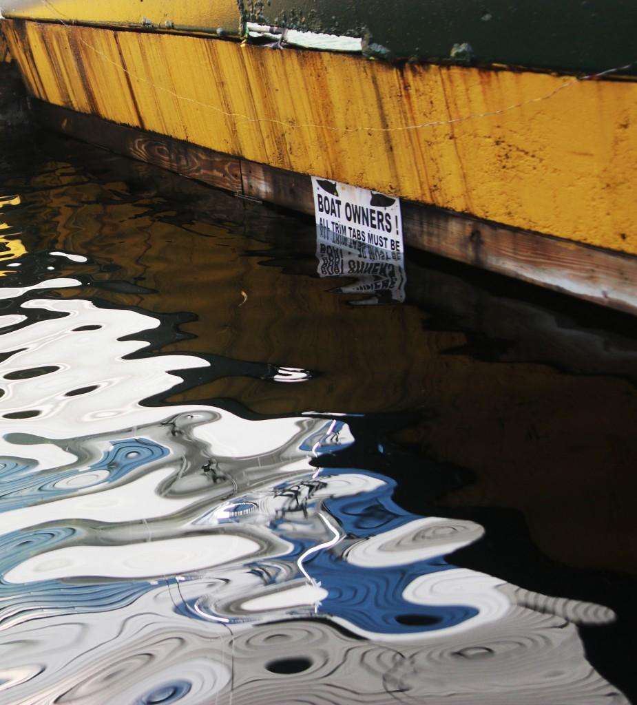 Rising sea levels have subsumed warning signs on a dock at Key Largo Harbor Marina.