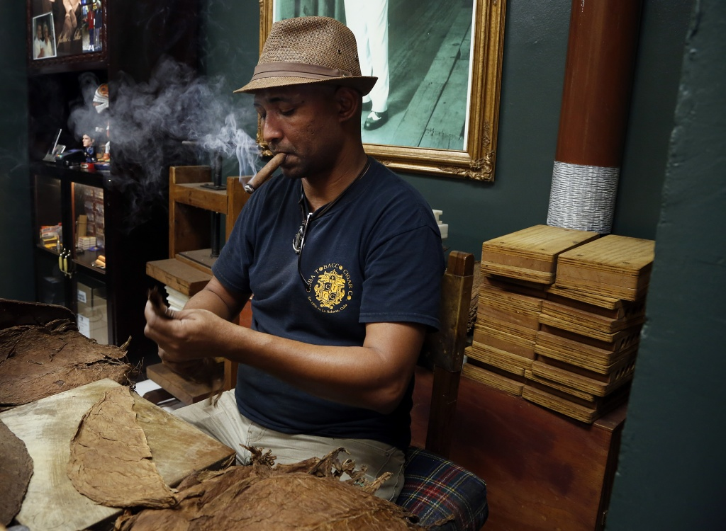 Adiocha Fernandez prepares tobacco leaves to roll at Cuba Tobacco Cigar Co. (Photo by Uma Chatterjee)