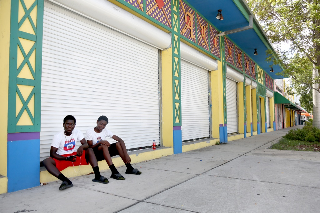 Evens Jean Joseph, 16, left, and William Oscar, 15, take a break on the streets of Little Haiti. (Photo by Anthony Fernandez)