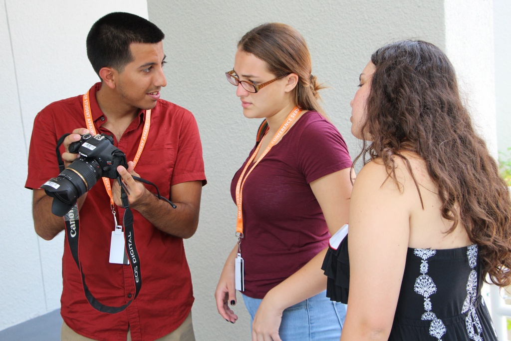 Counselor Tomás Monzón shows workshoppers Keilah Angueira and Marlowe Starling how to adjust a camera in preparation for a photo assignment.