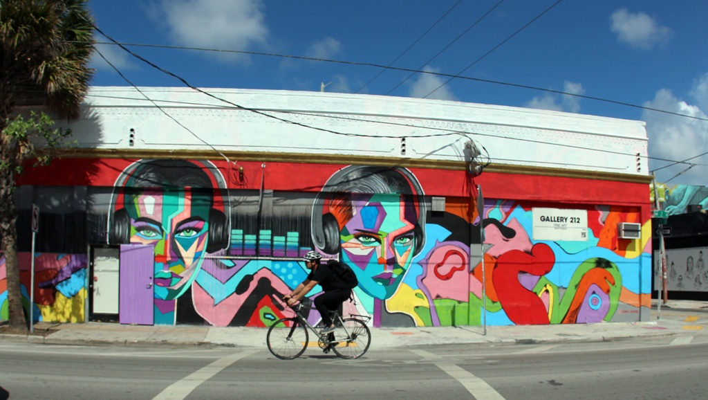 "NEIGHBORHOOD ART: A bicyclist rides by ""Gallery 212,"" one of the many art galleries in Miami's Wynwood neighborhood. (Photo by Christopher Vazquez)"