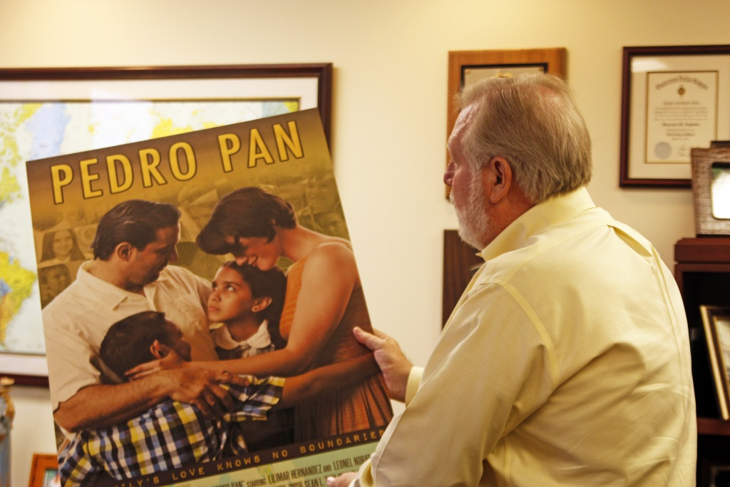 Frank Angones, president of the Florida Bar Association, views a poster of a film that chronicles the Cuban Pedro Pan exodus. (Photo by Matthew Remold)